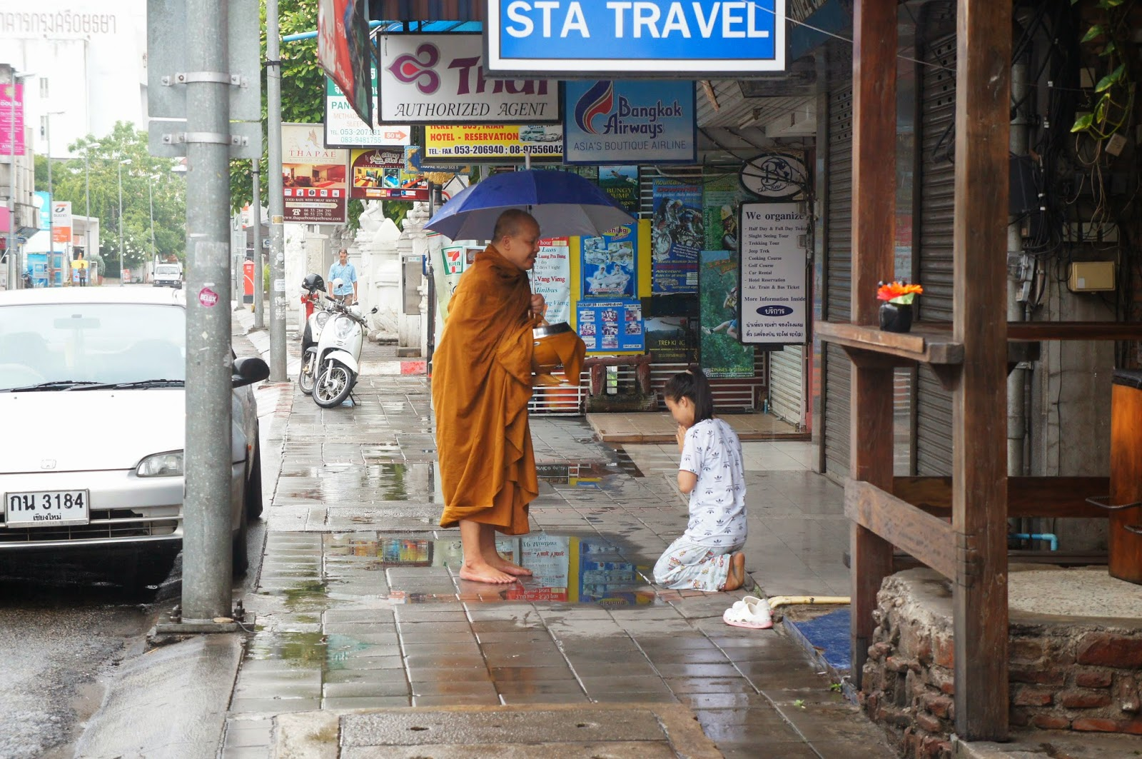 Chiang Mai - A monk gives a young woman a blessing after she gives him food