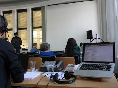 Dolmetscherin, Dolmetschpult, Rechner, Publikum