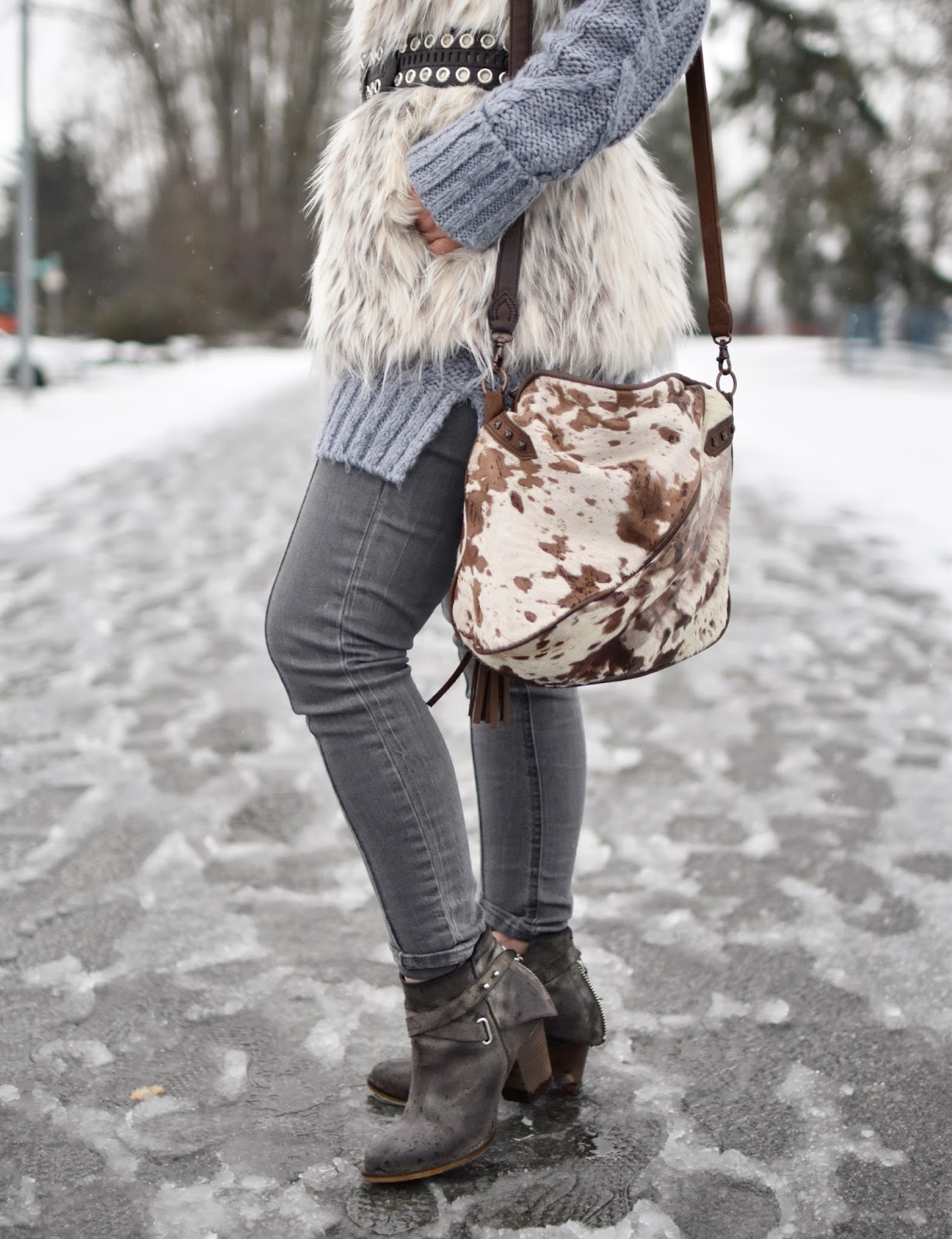 Monika Faulkner outfit inspiration - tunic sweater, belted faux-fur vest, grey skinny jeans, pony-hair bag