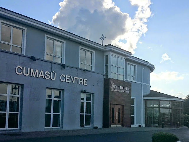 Picture of Cumasu centre Doughiska Galway - former hotel building converted into a church and community centre.  Two story building, floor to ceiling windows, round wooden conservatory.  Celtic cross on a cloudy background, rimmed by sunlight