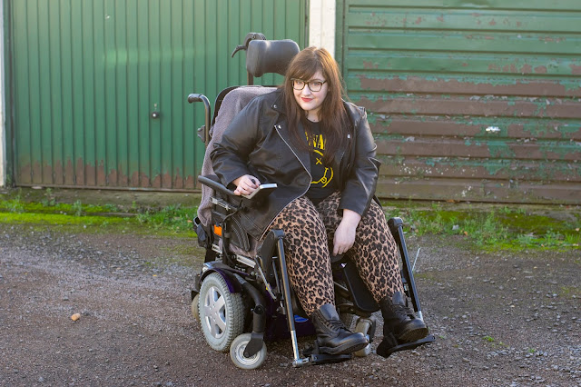 Woman sat in powerchair wearing leopard print trousers, Nirvana tshirt, leather jacket and Dr Martens boots