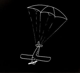 Un avión suspendido en el aire por un paracaídas