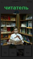 мальчик читатель около книжных полок с раскрытой книгой