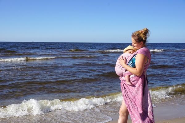 Zmiany w życiu rodzica - chusta tkana lenny lamb zaczarowana symfonia z lnem w Kołobrzegu na plaży. Dziecko w kangurze