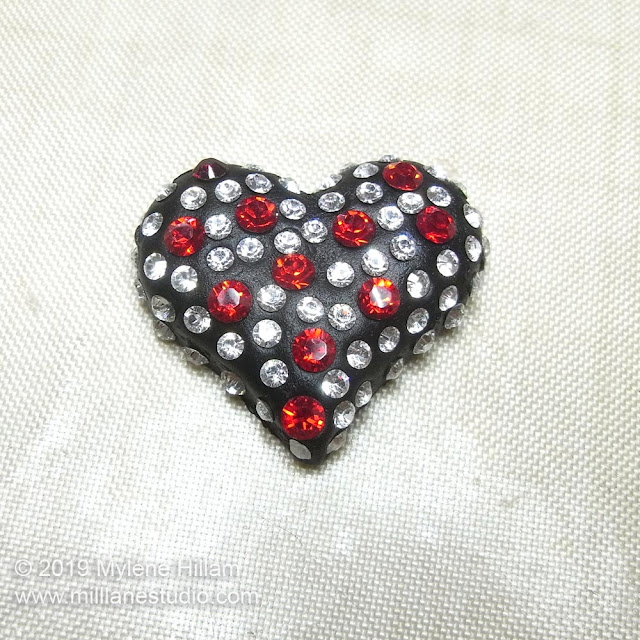 Black resin clay heart studded with Light Siam and clear crystals.