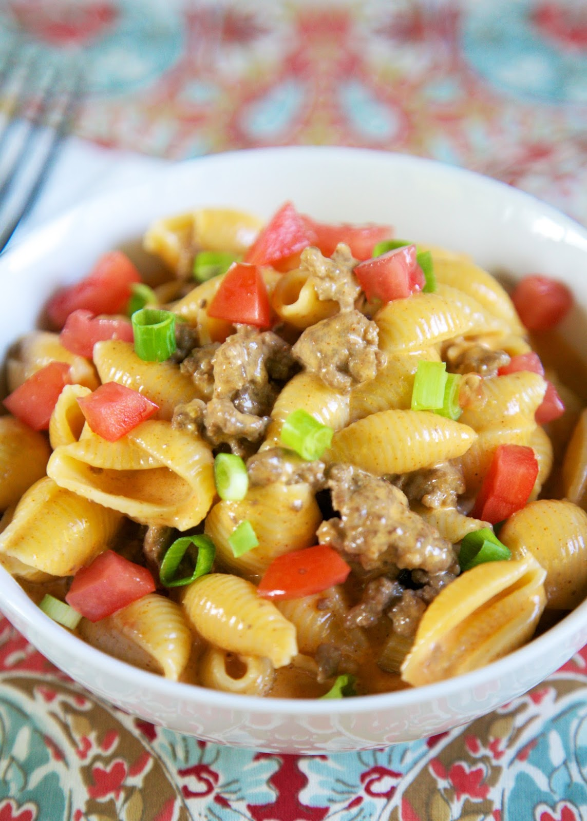 Beef Enchilada Macaroni and Cheese - quick Mexican recipe! Hamburger, pasta shells, heavy cream, enchilada sauce, cheese - top with tomatoes and green onions. Super simple and SO delicious! Ready in 10 minutes!