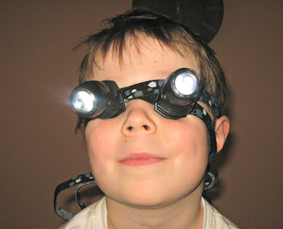 Boy wearing head torches on his eyes