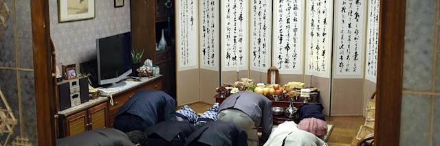Familia coreana haciendo reverencias a los antepasados por Chuseok