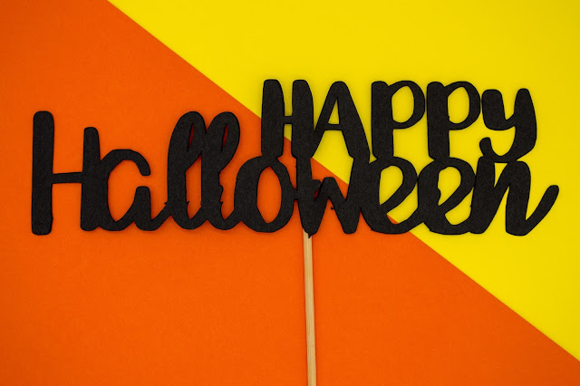 Black wording reading Happy Halloween, on a yellow and orange background