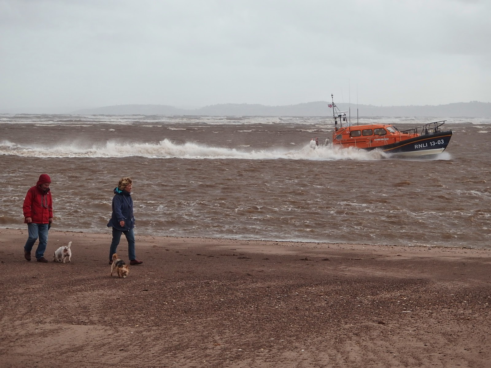 Walking the dog on Exmouth beach with the local lifeboat on manoevres in the background