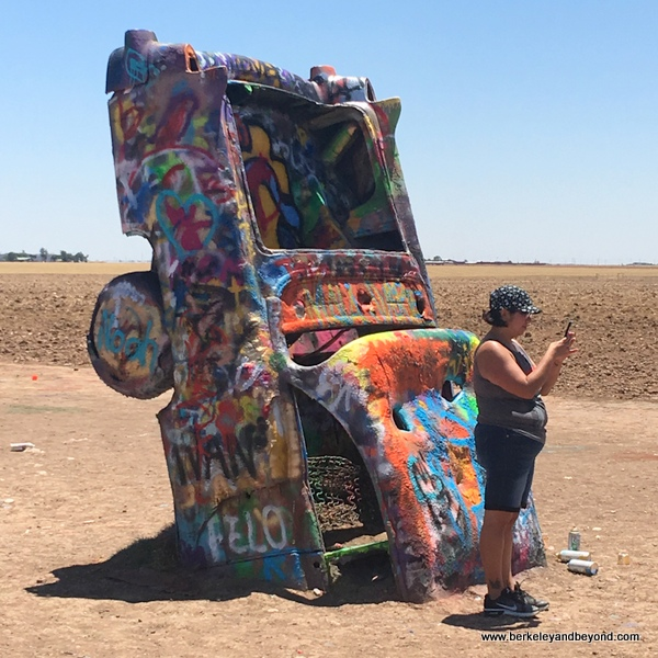 visitor taking a selfie at Cadillac Ranch in Amarillo, Texas