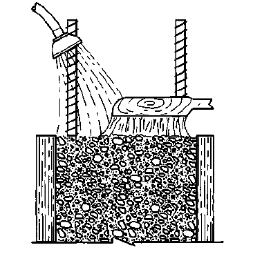Figure 1: Washing and brushing to remove laitance about two hours after placing of concrete.