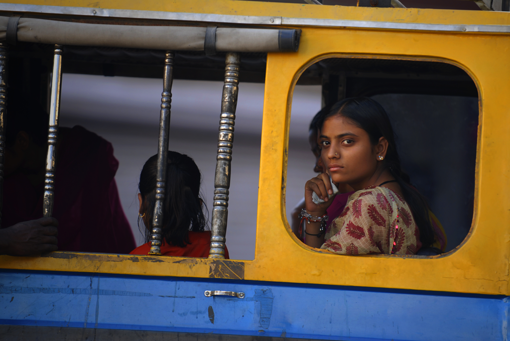 An Indian girl is looking out a bus window in Udaipur, India.