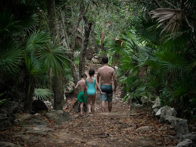 Hombre y dos niños de espaldas en un camino en la selva