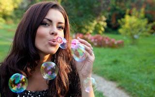 девушка пускает мыльные пузыри счастлива