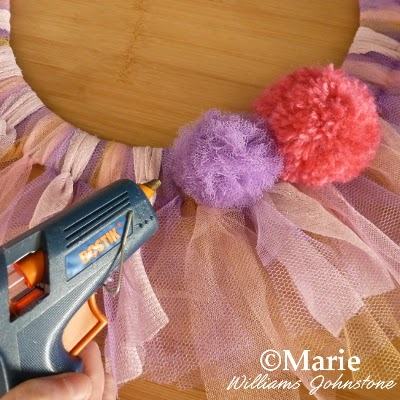 Glue gun sticks pom poms onto a handmade hanging decoration