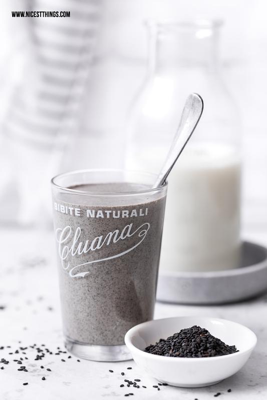 Glas mit grauem Smoothie / veganem Proteinshake aus schwarzem Sesam