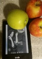 Das Cover zeigt ein Mädchen mit Kapuze. Als Deko hab ich um den Kindle drei Äpfel gelegt.