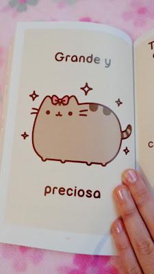 Fotografía de una página del libro de Pusheen, con la gatita gorda y grande, con un lazo rosa.