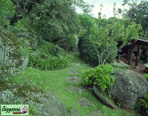 Caminho com pedras rústicas chapada que sai da residência e vai até a construção da churrasqueira com execução do paisagismo natural.