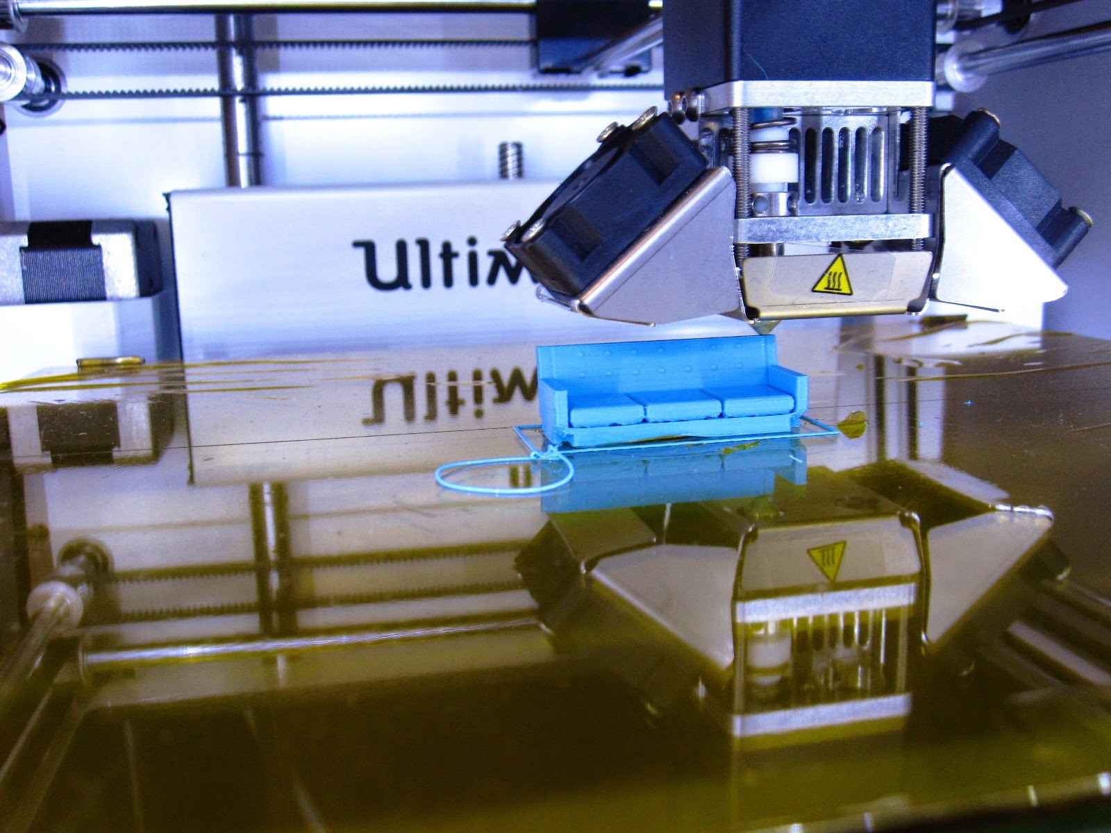 3D printer printing a miniature sofa.