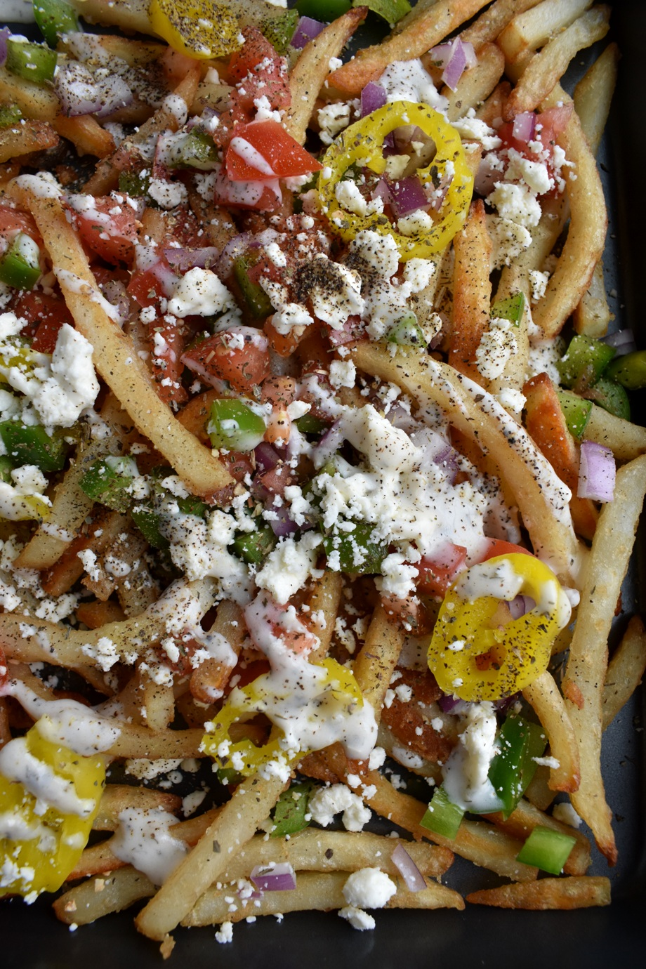 Loaded Greek Fries are ready in 25-minutes and topped with feta cheese, tomato, green pepper, red onion, banana peppers, drizzled in feta dill dressing and sprinkles in Italian spices for an easy appetizer, side dish or snack.