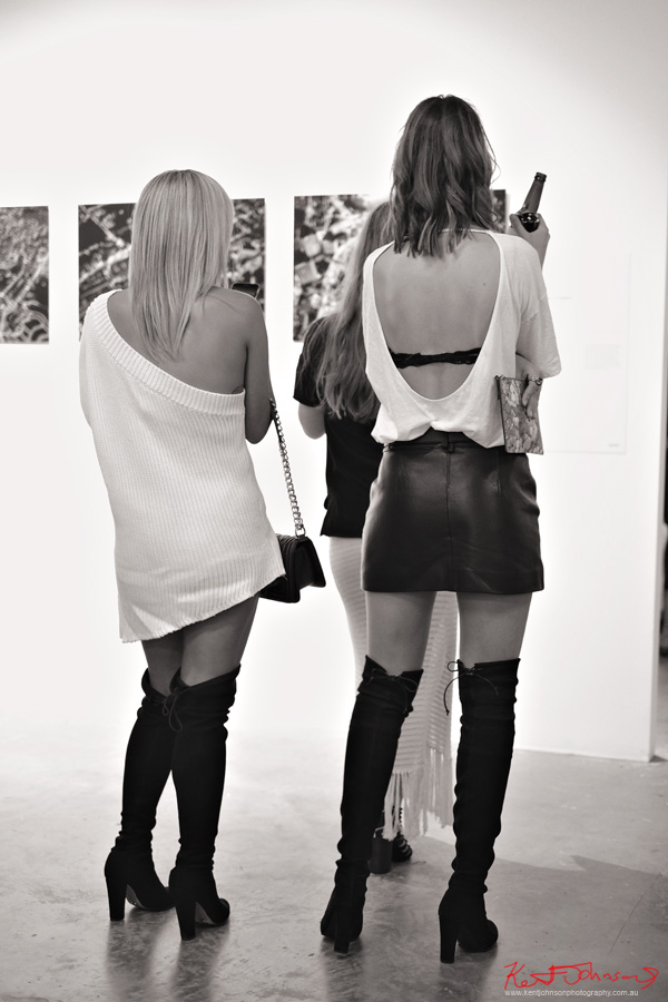 Three women wear coordinated black and white outfits at an art opening at aMBUSH Gallery. Photo by Kent Johnson for Street Fashion Sydney.