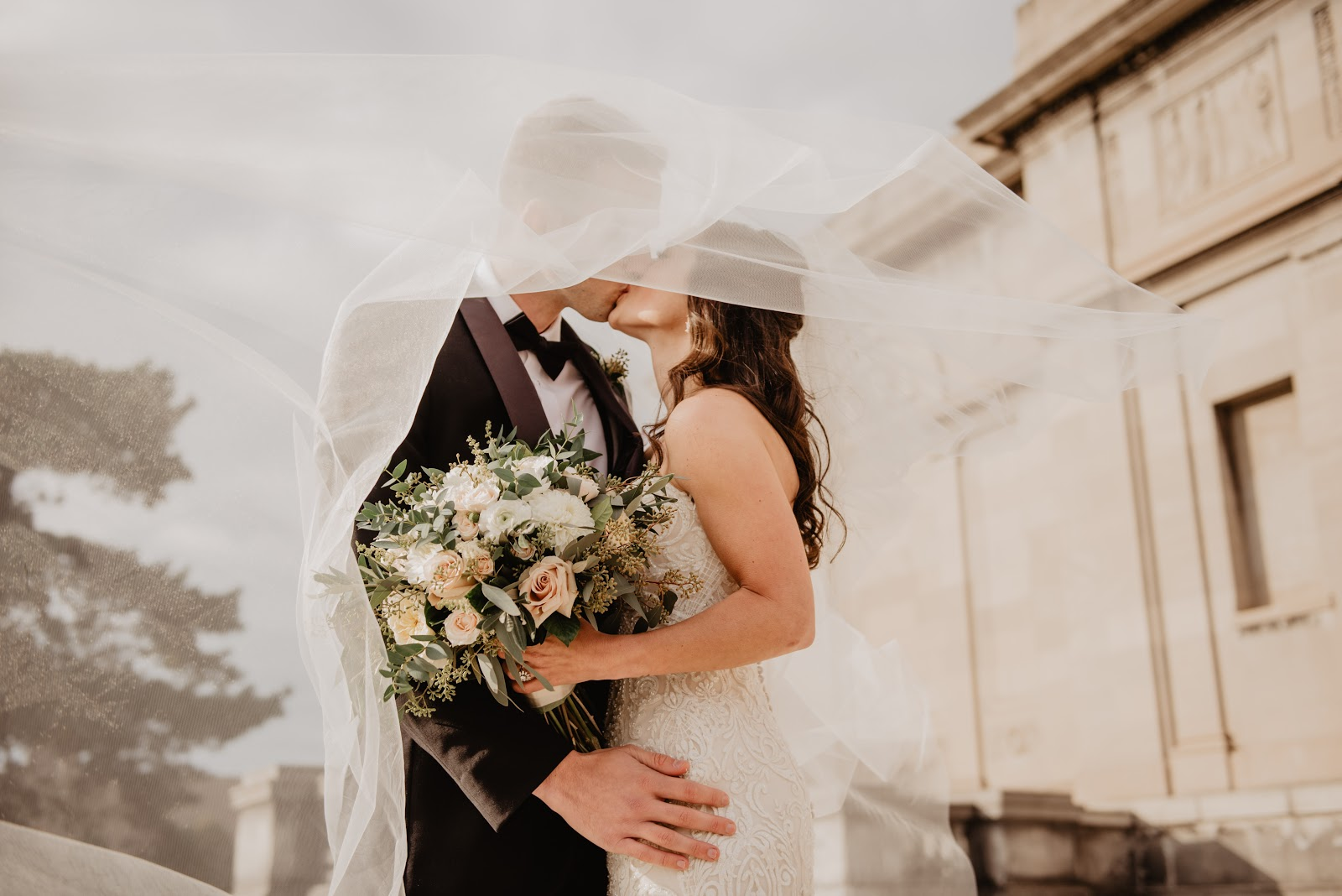 結婚式で口付けを交わす黒いタキシードの男と白いドレスの女に白いベールがかかっている