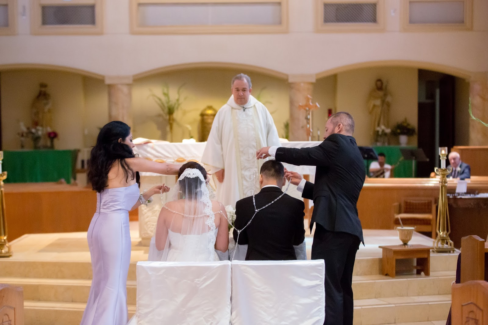 Priest Blessing Bride and Groom with Best Man's and Maid of Honor's Help