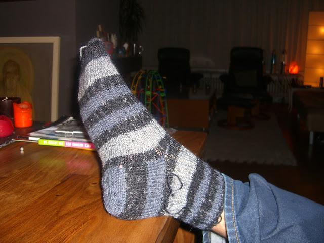 Gebreide sok aan voet, net af, draadjes zitten er nog aan.