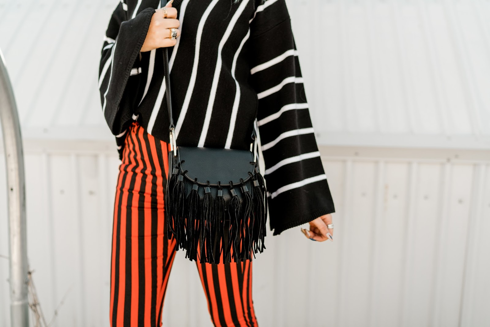 fringe purse, black purse, striped pants