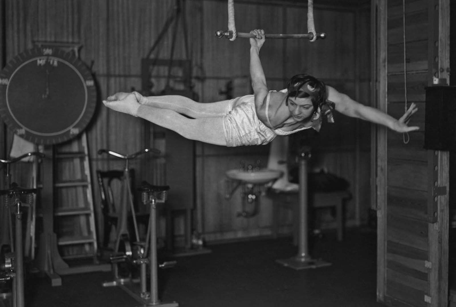 A woman using an apparatus in the gymnasium of the ocean liner S.S. Bremen. 1930s.