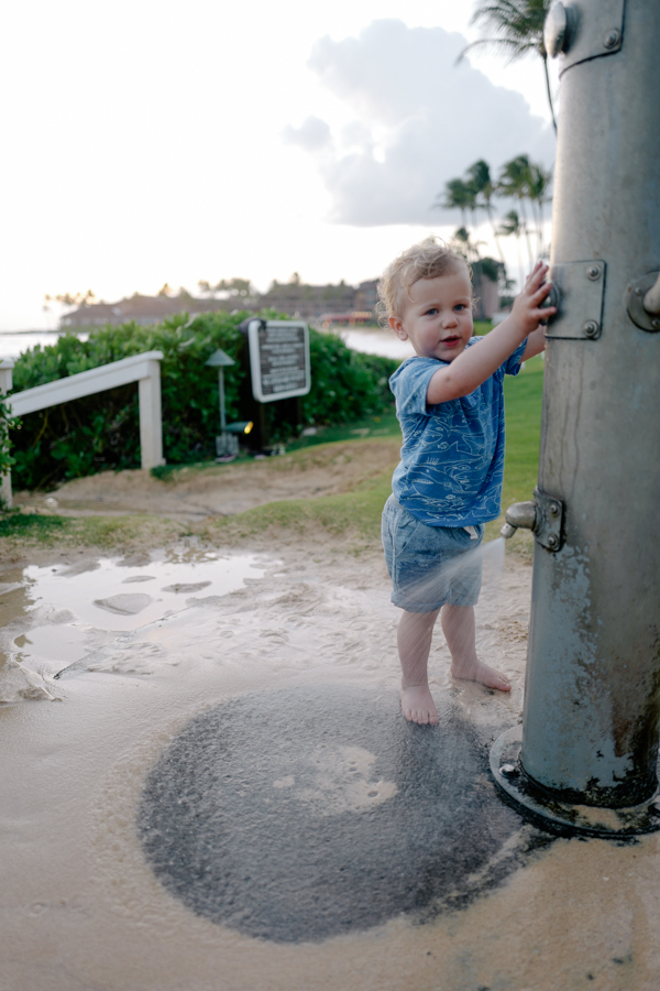 Toddler loving the outdoor showers at Kiahuna Plantation, Kauai