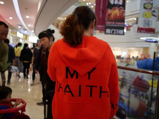 "woman wearing a ""MY FAITH"" sweatshirt"