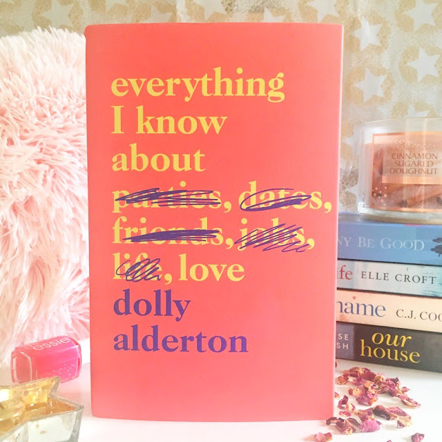 stack of books in the background with a pink fluffy pillow, nail polish on the left side, Dolly Alderton Everything I Know About Love book at the front with rose petals on the right side scattered