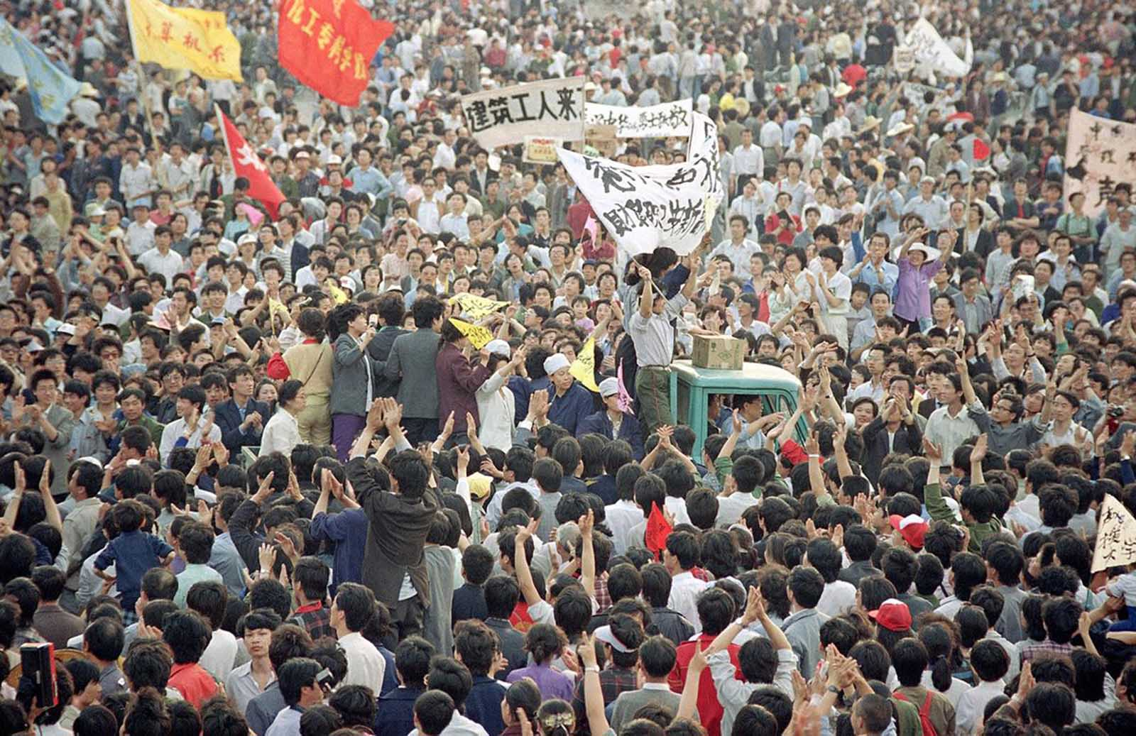 A truck is almost buried in people as it makes its way through the crowd of thousands gathered in Tiananmen Square in a pro-democracy rally, on May 17, 1989.