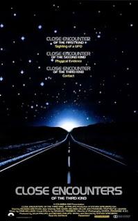 Cartel de Encuentros en la tercer fase (Spielberg, 1977). Muestra los créditos y arriba una oscura carretera, en el horizonte hay una intensa luz blanca