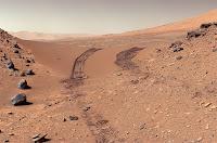 Üzerinde bir keşif aracının tekerlek izleri olan Mars yüzeyi fotoğrafı