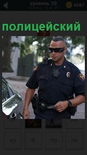 Около машины стоит полицейский в форме и темных очках и с рацией на плече