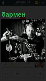 За стойкой  в развлекательном заведении стоит бармен и приготавливает очередной коктейль для посетителей