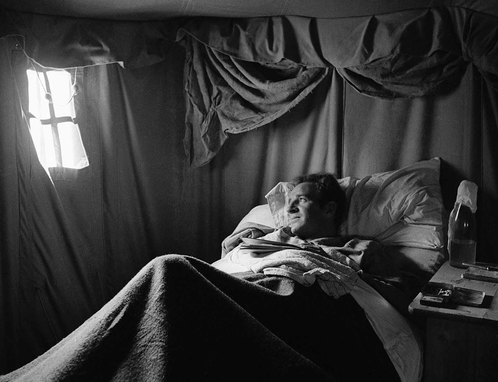 A wounded British warrior in Libya lies on cot in a desert hospital tent, on June 18, 1942, shielded from the strong tropical sun.