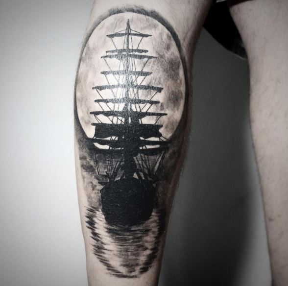 This Ship Tattoo Design On The Calf Of This Guy Is Beautifully Inked As The Artist Used The Negative Colors To Show A Ship Sailing With A Full White Moon In