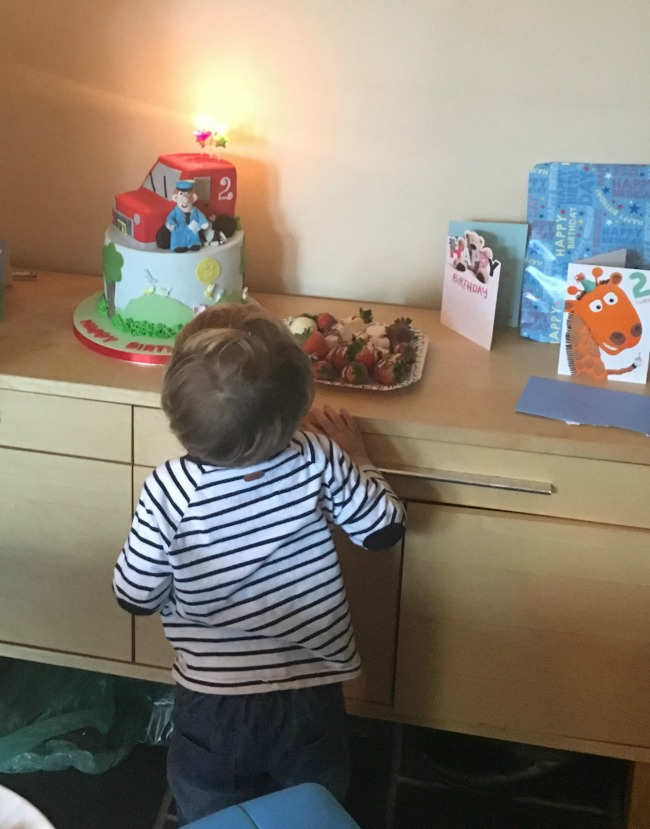toddler-blowing-out-candles-on-postman-pat-birthday-cake