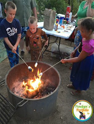 Three children standing around a fire, roasting marshmallows for smores