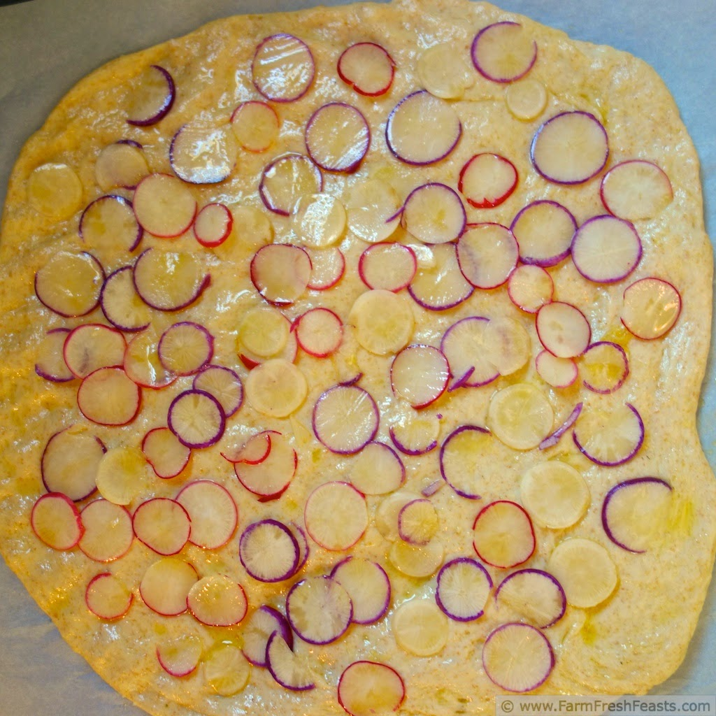 Thinly sliced radishes with feta, goat cheese, and shredded cheeses in a spring radish pizza.