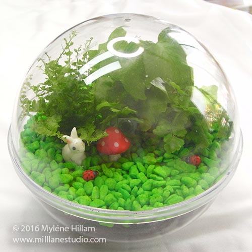 Lindt Maxi Ball container filled with mini ferns, bright green pebbles and rabbit and toadstool figurines.