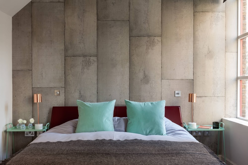 teal-cushions-concrete-wall-industrial-bedroom