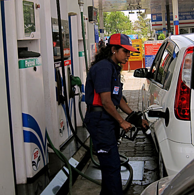woman attendant filling gas into car
