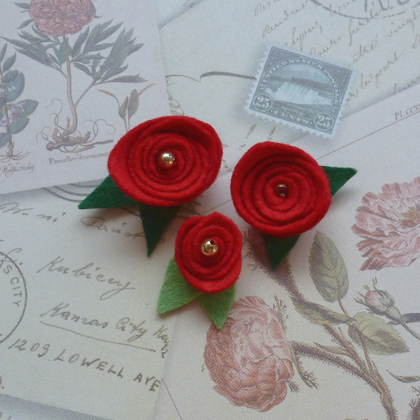 iny red felt roses with beads and green leaves on floral paper background learn how to sew and make small felt rose flowers