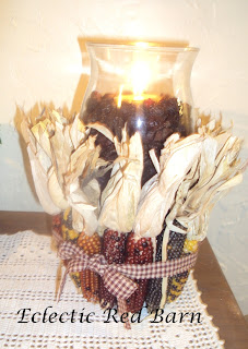 hurricane candle holder with indian corn wrapped with ribbon